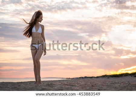 Beautiful girl in a swimsuit on the beach at sunset