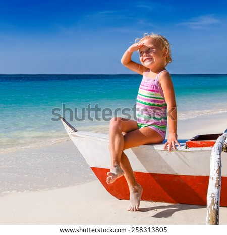 Beautiful girl in a swimsuit sitting on the boat and looks into the distance - stock photo