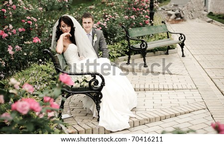 beautiful girl in a wedding dress and the groom sitting among the roses