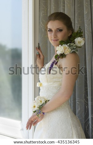 Beautiful girl in a wedding dress. Hairstyle decorated with fresh flowers. Her wrist is decorated with fresh flowers as well.