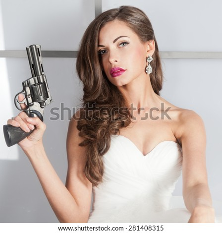 beautiful girl in a wedding dress with a gun, studio shooting - stock photo