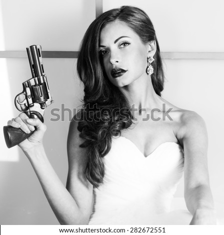 beautiful girl in a wedding dress with a gun, studio shooting. Black and white image. - stock photo