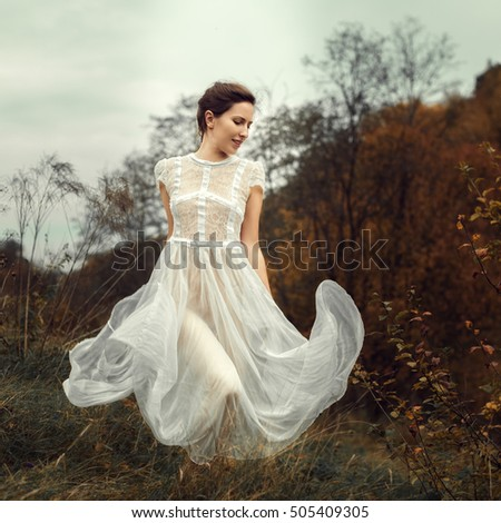 Beautiful girl in a white dress and autumn