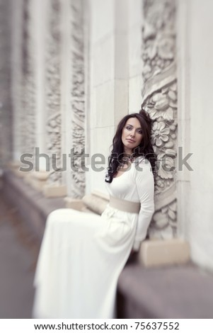 beautiful girl in a white dress near to white antique arches - stock photo