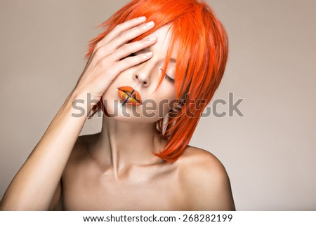 Beautiful girl in an orange wig cosplay style with bright creative lips. Art beauty image. Portrait shot in the studio. - stock photo