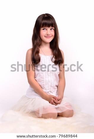 Beautiful girl in angelic costume sitting on white cloud - stock photo