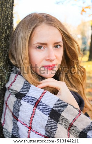 Beautiful girl in autumn forest reading a book covered with a warm blanket