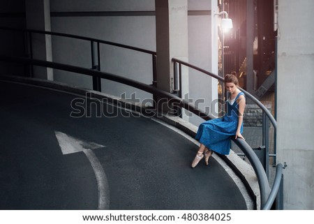 Beautiful girl in ballet shoes standing on concrete balcony