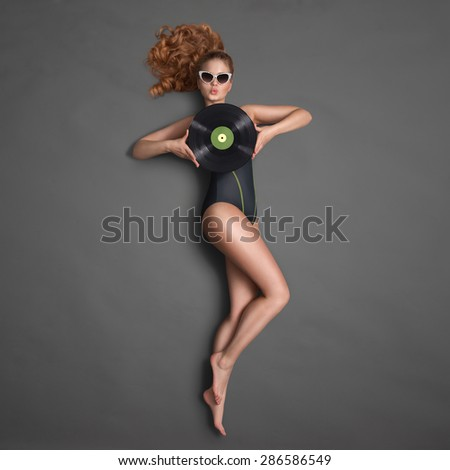 Beautiful girl in bikini and sunglasses, holding an LP microgroove vinyl record and sending a kiss on chalkboard background. - stock photo