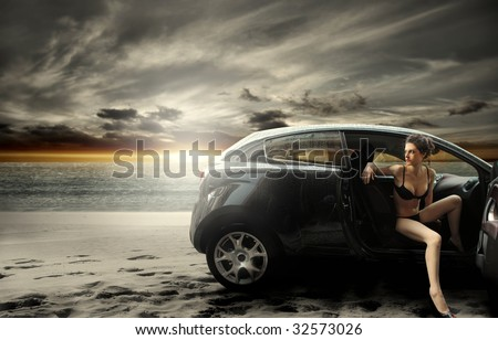 beautiful girl in bikini arriving on the beach with car - stock photo