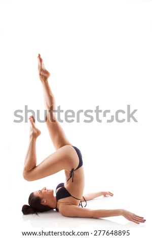 Beautiful girl in bikini doing shoulder stand. Caucasian woman doing yoga. Sarvangasana asana. - stock photo