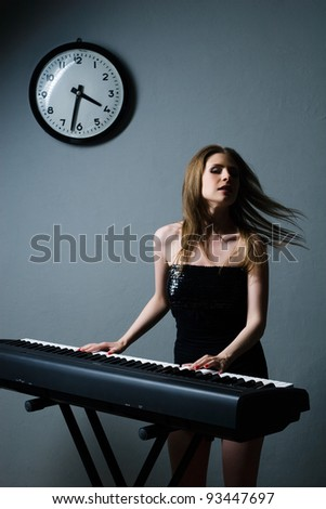 beautiful girl in black dress playing on keyboard