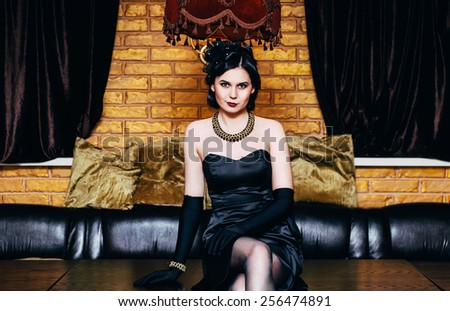 Beautiful girl in black dress sitting on the table. Party in gangster style. - stock photo