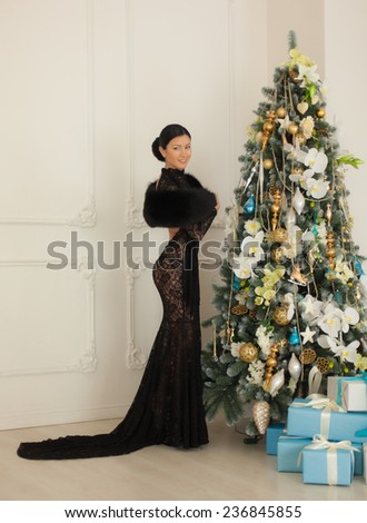 Beautiful girl in black dress standing at the Christmas tree. - stock photo