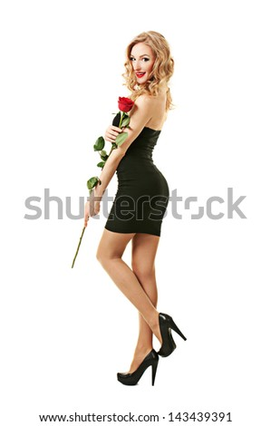 Beautiful girl in black dress standing with rose - stock photo