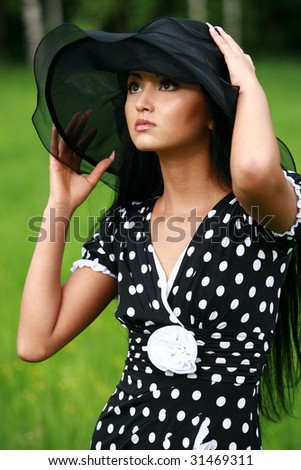 Beautiful girl in black hat nd dress in nature - stock photo