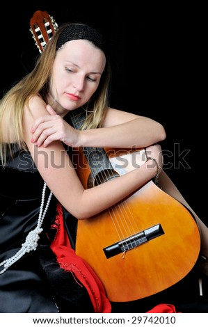 Beautiful girl in black kerchief with a guitar, on black background - stock photo