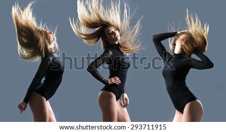 Beautiful girl in black kombidress rhythmically moves. Studio photo isolated on gray. - stock photo