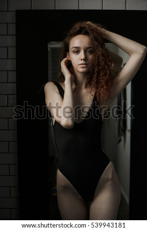 Beautiful girl in black swimsuit in bathroom. Shower. Sexy, charming Girl posing in bathroom. Long Red hair. Fashion portrait. Black background.