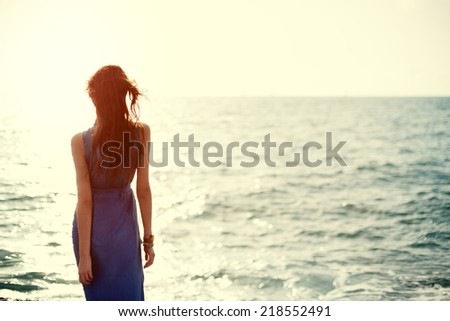 beautiful girl in blue dress near the ocean looking at the sunset - stock photo