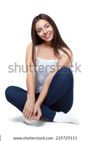 beautiful girl in blue jeans and white shirt sitting on a white background isolated - stock photo