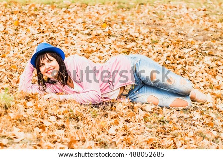 Beautiful girl in blue jeans lying on yellow leaves in the autumn park