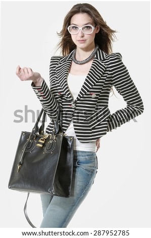 Beautiful girl in blue jeans with bag posing - stock photo