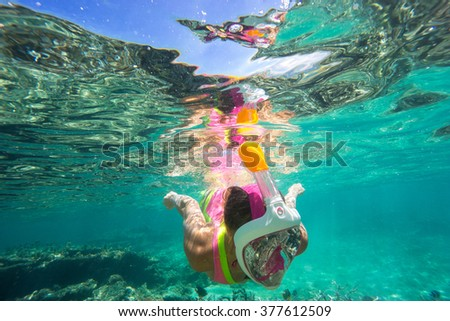 Beautiful girl in bright bikini with white hair has been snorkeling on the island of Mauritius in the Indian Ocean. She feeds the fish under water in clear turquoise water - stock photo