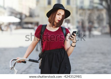 Beautiful girl in burgundy shirt, black skirt and hat with bicycle, phone and bag looking at camera. Cycling, outdoor, city