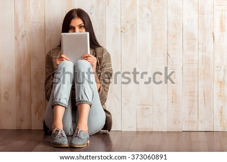 Beautiful girl in casual clothes hiding behind the tablet and looking in camera while sitting against wooden background - stock photo