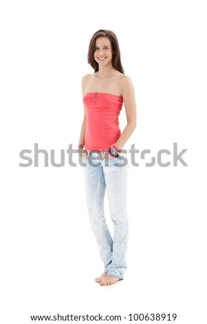 Beautiful girl in casual summer top, jeans, bare foot, smiling at camera with hands in pocket, full length, isolated on white.
