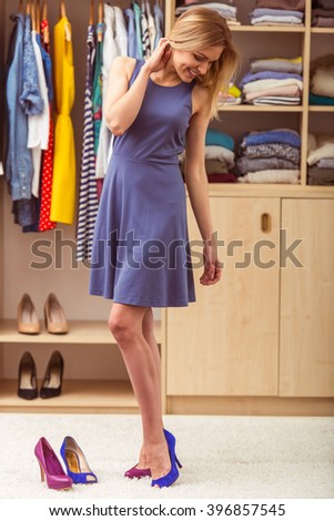 Beautiful girl in cocktail dress is smiling while trying on high heel shoes in her dressing room - stock photo
