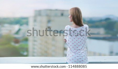 beautiful girl in cold weather is on the roof - stock photo