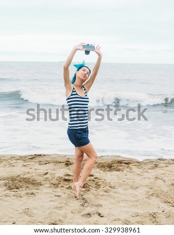 Beautiful girl in costume of sailor and paper ship in hairstyle doing selfie with vintage photo camera on beach in summer, pin-up image - stock photo