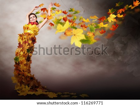Beautiful girl in dress from autumn leaves on  abstract windy background - stock photo