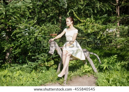 beautiful girl in dress sitting on a funny little wooden horse in the park - stock photo