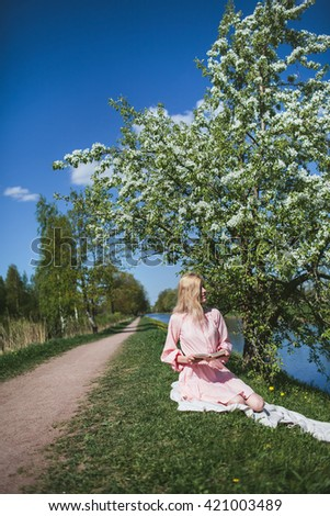 beautiful girl in dress sitting with diary under the apple blossom