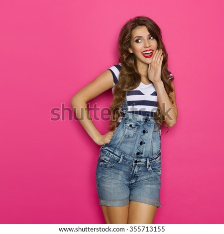 Beautiful girl in dungarees and stripes shirt shouting and holding hand on chin. Three quarter length studio shot on pink background. - stock photo