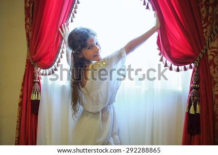 Beautiful girl in ethnic dress opens the red curtains on the window - stock photo