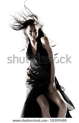 Beautiful girl in evening dress with hair blowing on white background