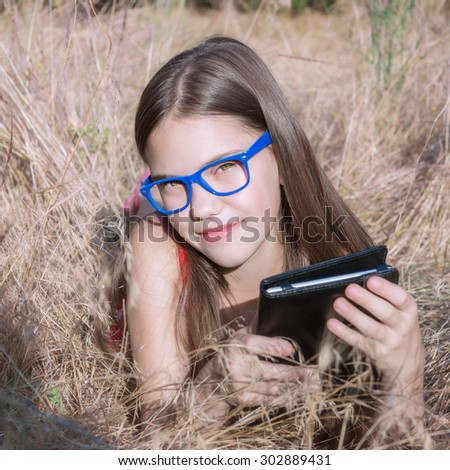 beautiful girl in glasses with an e-book in the hands of lay - stock photo