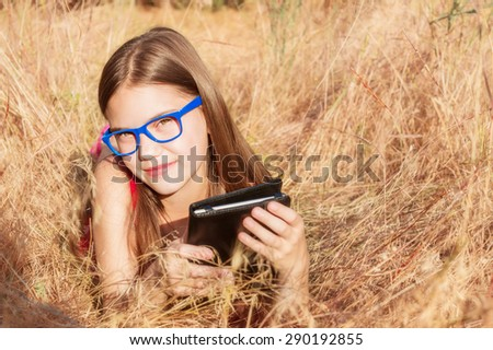 beautiful girl in glasses with an e-book in the hands of lay in the dry grass - stock photo