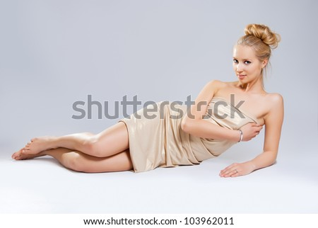 Beautiful girl in gold dress lying on a white background - stock photo