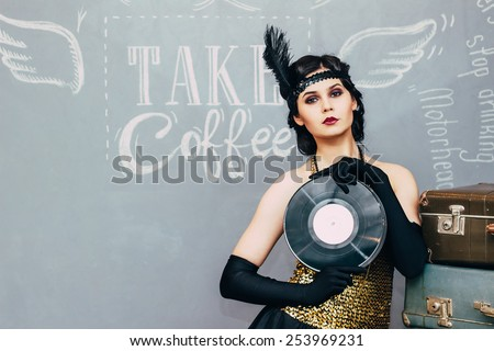 Beautiful girl in golden dress, holding an old plate in his hands. Party in style gangsters forties. - stock photo