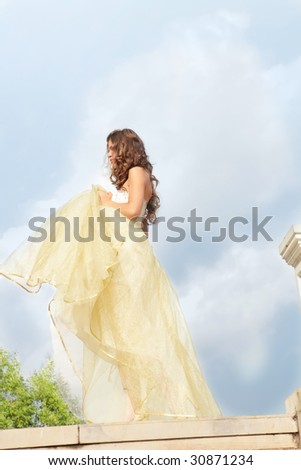 beautiful girl in golden dress under blue sky - stock photo