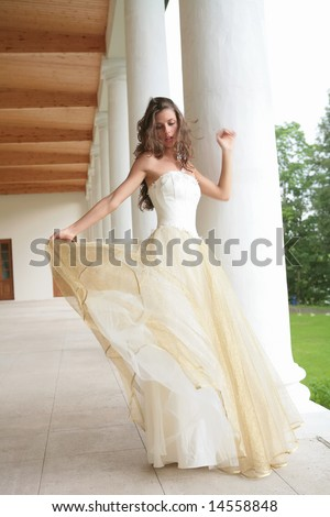 beautiful girl in gown of the bride dances between pillar of the old-time building
