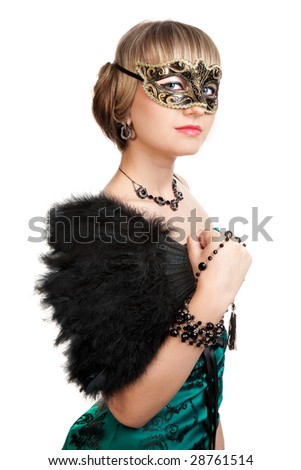 Beautiful girl in green evening dress with necklace and earrings  in carnival mask holding fan and beads