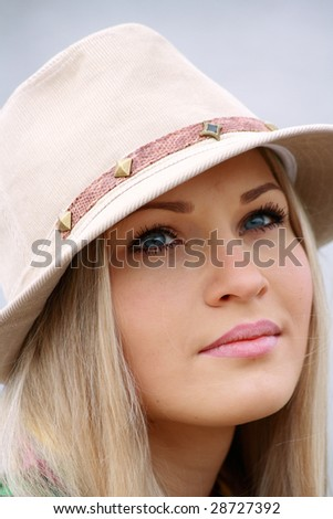 beautiful girl in hat on coast lake