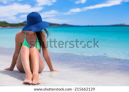 Beautiful girl in hat relaxing at white sand tropical beach