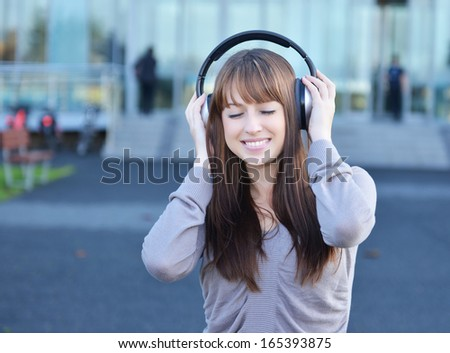 Beautiful girl in headphones over urban background - stock photo